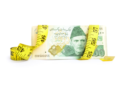 withholding: Closeup of five hundred rupee Pakistani currency bill with measure tape for budget cut concepts