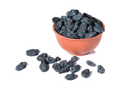 Black raisins in a clay cup on a white background.
