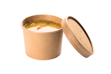 Pea soup in a disposable paper cup from craft paper Imagens