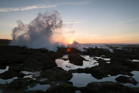 Splash of ocean waves against a background of sunset and rocks