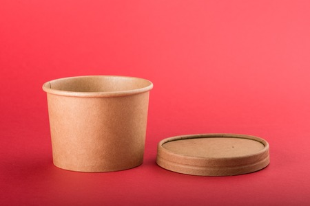 Disposable paper container with cap for soup on a red background