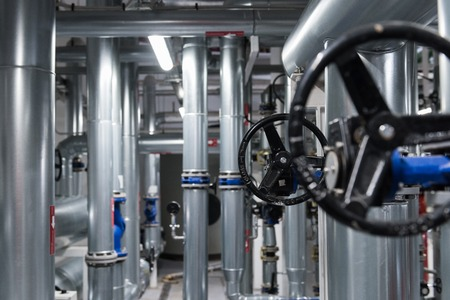 Fondo de ingeniería abstracta con válvulas negras y tubos metálicos. Foto de archivo
