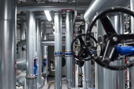 Formation abstraite en ingénierie avec vanne noire et tuyaux métalliques. Banque d'images