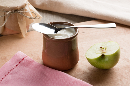 White homemade yogurt in a clay jar with an apple