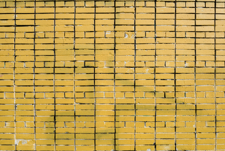 Yellow brick wall with traces of white paint. Imagens - 125423266