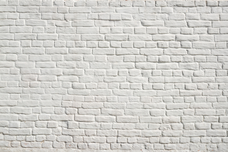 White brick wall with smooth seams, covered with lime or plaster
