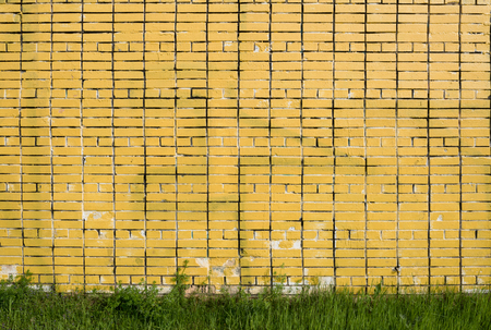 Yellow brick wall with grass at the base.