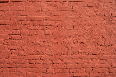 Red brick wall with smooth seams, covered with lime or plaster