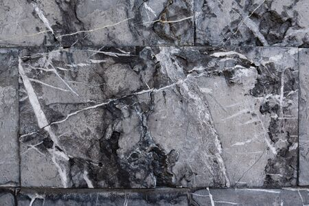 Background from gray marble blocks. A wall of rough stone with black potholes and white lines.