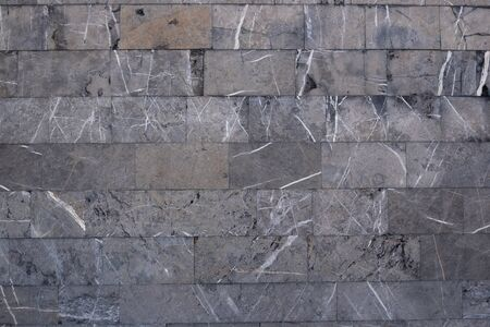 Background from gray marble blocks. A wall of rough stone with black potholes and white lines. Imagens - 128605768