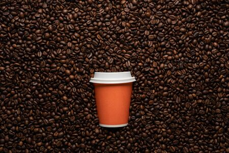Orange disposable cup to go, on the background of coffee beans with empty space for text