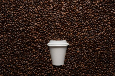 White cup to go on the background of coffee beans with empty space for text Imagens