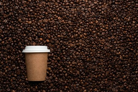 disposable cup to go, on the background of coffee beans with empty space for text Imagens