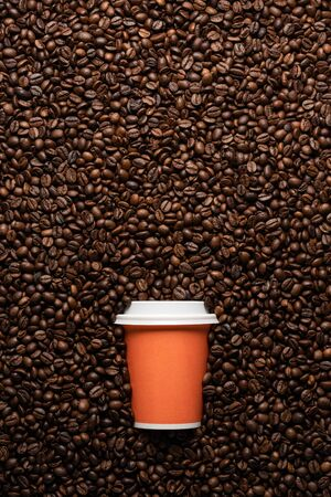 Orange disposable cup to go, on the background of coffee beans with empty space for text Imagens - 128656811