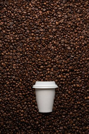 White disposable cup to go, on the background of coffee beans with empty space for text.