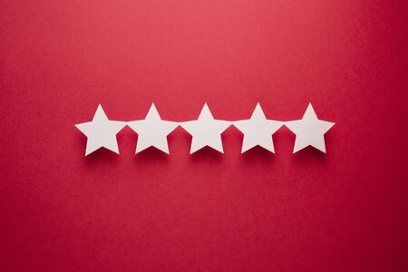 Feedback concept. Five white paper stars of approval on a red background