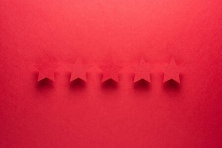 Feedback concept. Five red paper stars of approval on a red background