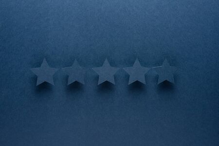 Feedback concept. Five blue paper stars of approval on a blue background