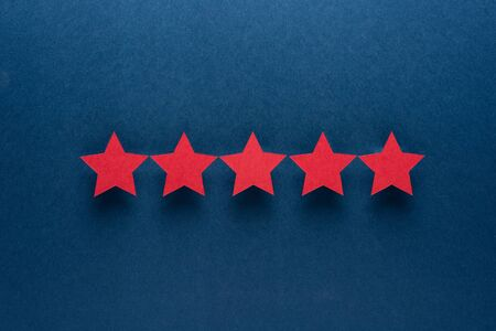 Feedback concept. Five red paper stars of approval on a blue background Stock Photo