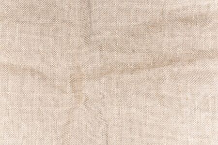 The texture of natural canvas. Background from rough fabric with small folds. Imagens - 133156045