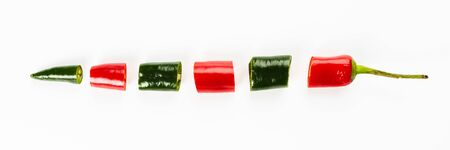 Cut pieces of red and green peppers isolated on a white background