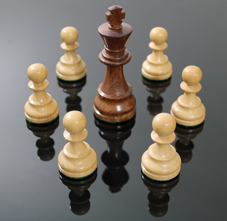 surrounded: Dark, wooden chess king surrounded by light colored pawns. Stock Photo
