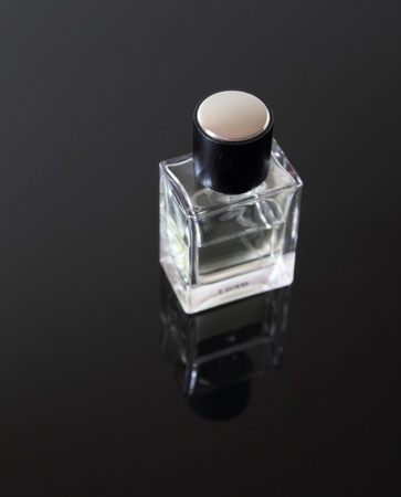 34 angled view of an unmarked, glass cologne bottle on a smoked glass table.