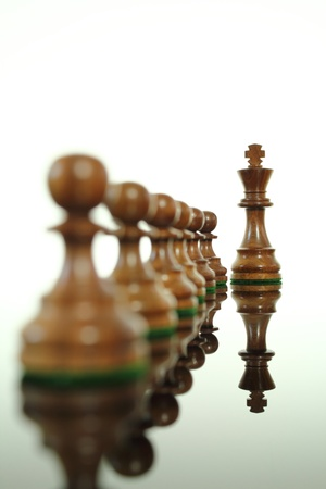 chess king: Chess king standing out from his pawns.