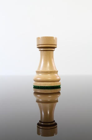 Tan wooden chess castle on a reflective glass table. Stock Photo - 10544705