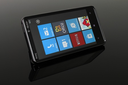 windows: Angled shot of an HTC HD7 running Windows Phone 7 on a reflective, smoked glass table.