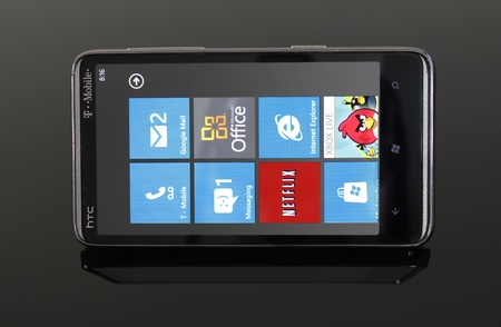 htc: Picture an HTC HD7 running Windows Phone 7 on a reflective, smoked glass table.