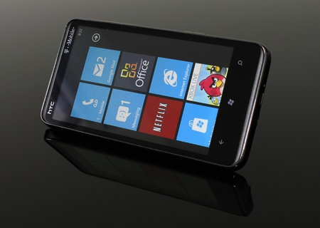 htc: Angled shot of an HTC HD7 running Windows Phone 7 on a reflective, smoked glass table.