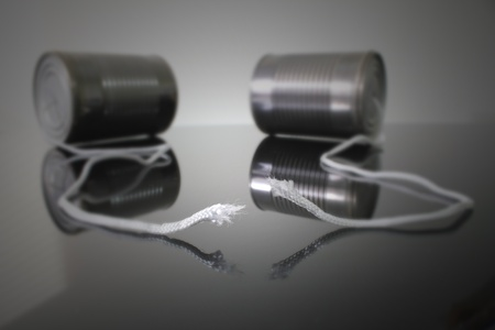 disconnection: Tin can telephone with focus on the broken string. Stock Photo
