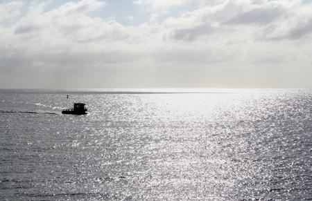 tug boat: Evening tug boat at sea with cludy skys.