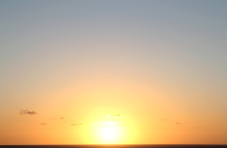 Sunset over the Caribbean sea with a few clouds.