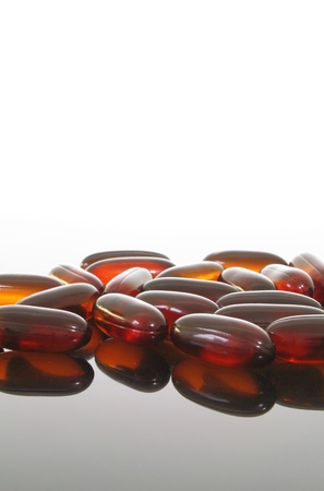 flaxseed: Group of flaxseed oil pills on a glass table. Stock Photo