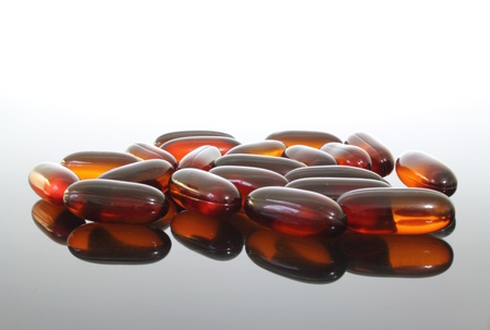 A group of flaxseed oil pills on a glass table.