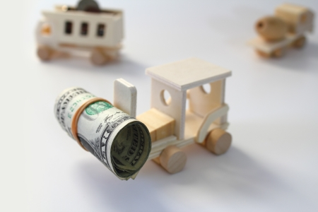 Toy, wooden forklift lifting a roll of money with dump truck and cement truck in the background. photo