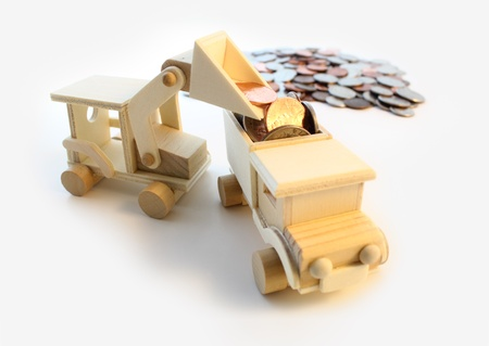 back hoe: Toy, wooden back hoe loading us coins into the back of a truck. Stock Photo