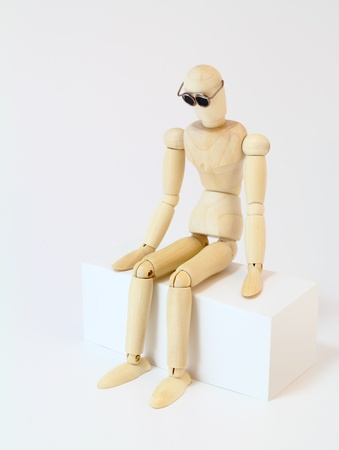 heartsick: Wooden character with glasses staring, sitting in deep thought.