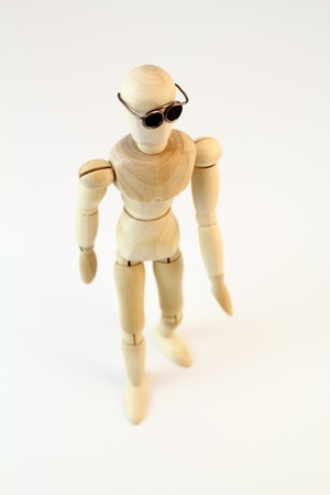 High angle view of a wooden character walking with glasses on.