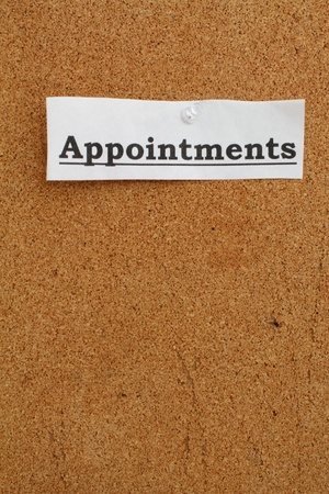 pin board: White strip of paper with the word appointments pinned to a cork board.