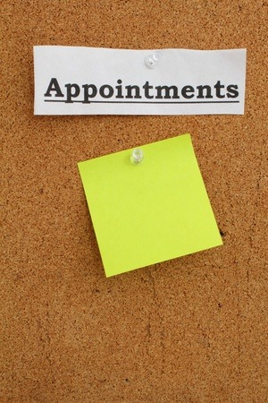 White strip of paper with the word &quot, Appointments&quot, pinned to a cork board with a post it note underneath. Stock Photo - 12363414