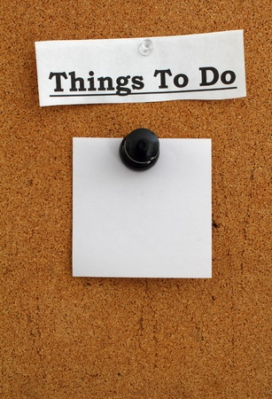 paper pin: Blank note paper pinned with a giant pushpin to a brown cork board with Things to Do as the heading.