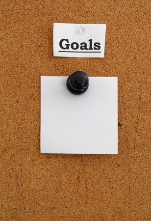 The word Goals and a blank note square pinned to a brown cork board. photo