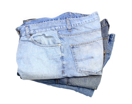 Isolated shot looking down on three pairs of stacked, weathered blue jeans
