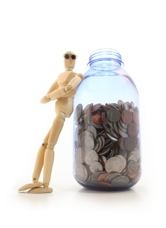 prudent: Wooden, posable artist manikin with glasses leaning against a jar full of us coins