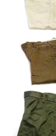 Folded khaki pants of different types on white  Фото со стока