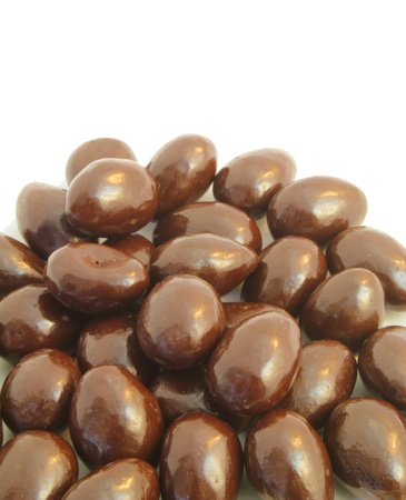 Vertical shot of chocolate covered almonds with white copy space. Banco de Imagens