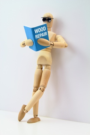 Wooden artist manikin reading a book on wood repair while leaning on a wall.